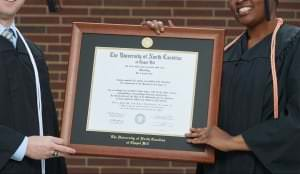 A Diploma In A Diploma Frame Being Shown Off For Photo